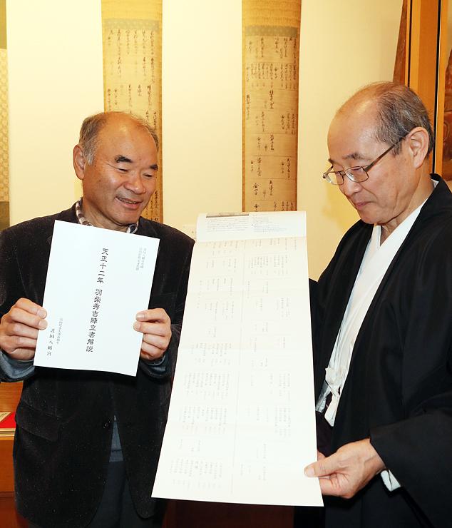 陣立書の前で解説書を手にする埴生宮司(右)と高岡さん=埴生護国八幡宮宝物殿