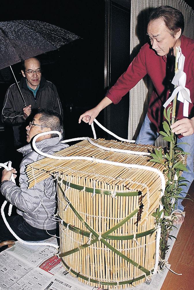 小西さん(右)に届けられた鵜様を収める籠=七尾市鵜浦町