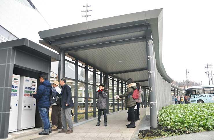 自動券売機で野沢温泉ライナー(右奥)の乗車券を購入する観光客ら