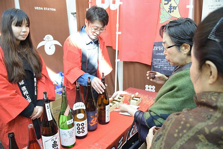 電車を待つ間、上田市の地酒を飲み比べる地元住民ら(右側)
