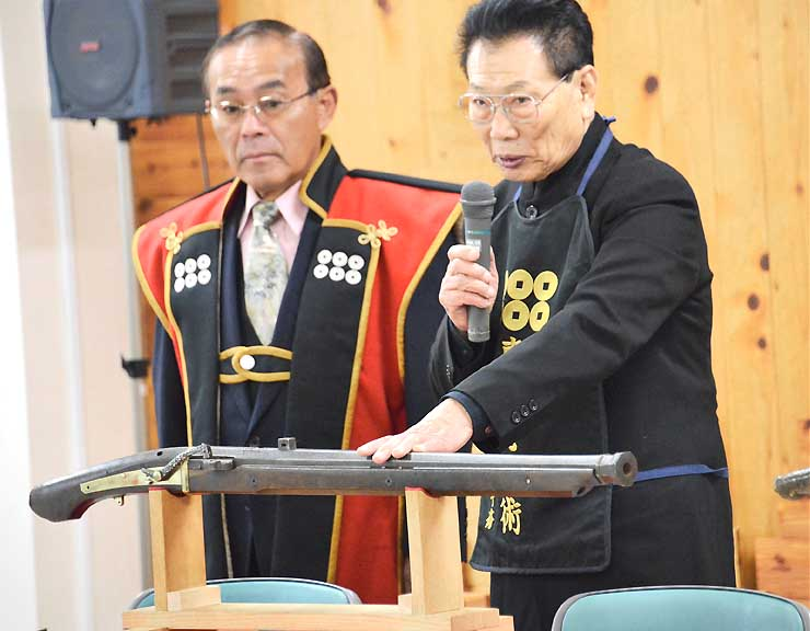 杉山弥一郎作の火縄銃について説明する沢田さん(右)