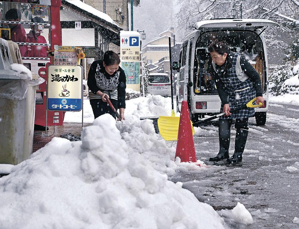 除雪に励む商店街の関係者=金沢市湯涌町