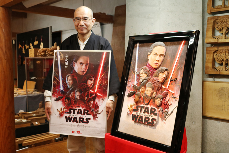 鳥越さん(左)が制作した彫刻ポスター(右)=井波彫刻総合会館