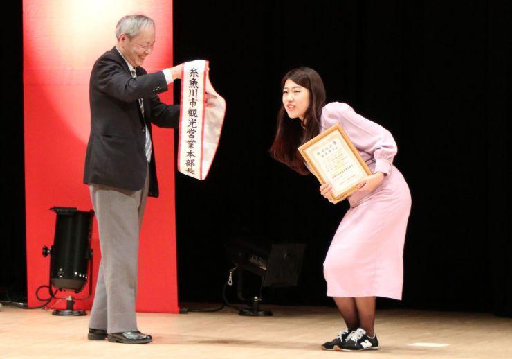 「糸魚川市観光営業本部長」の就任証とたすきを受け取る横沢夏子さん=12日、糸魚川市一の宮1