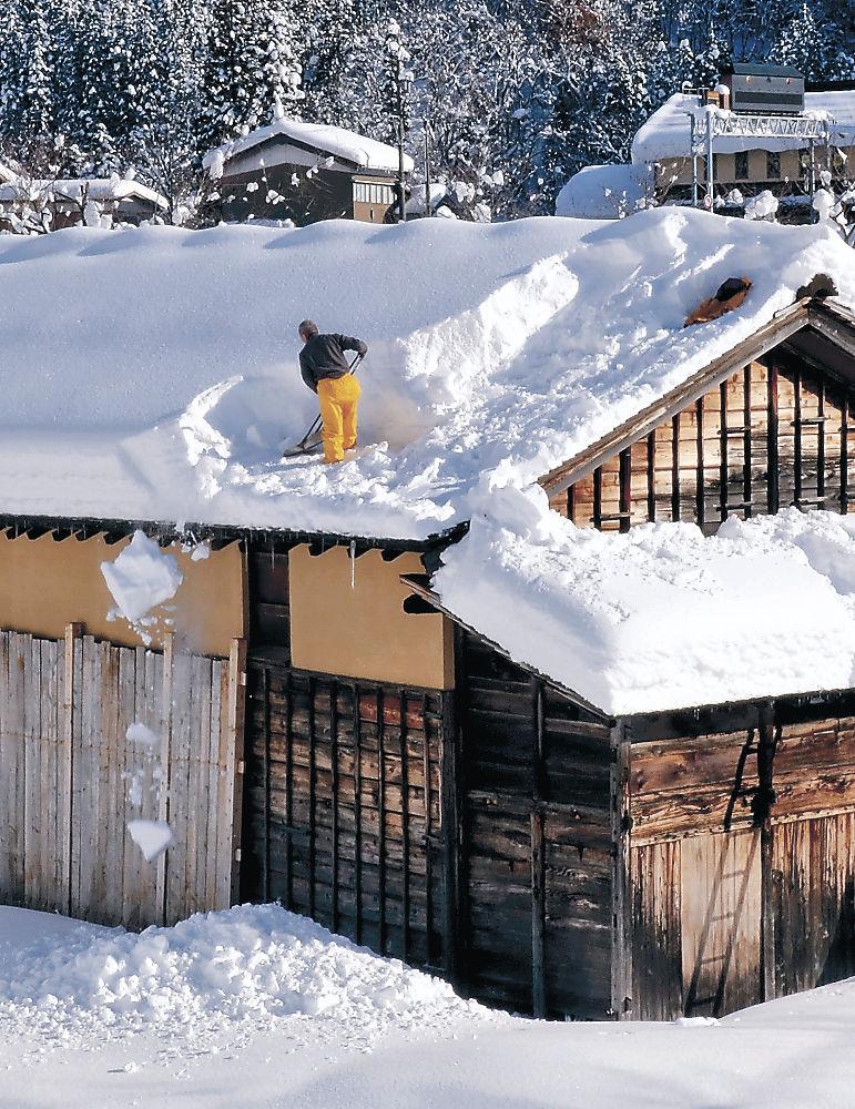 古民家の屋根雪を下ろす職員=白山市白峰の県白山ろく民俗資料館