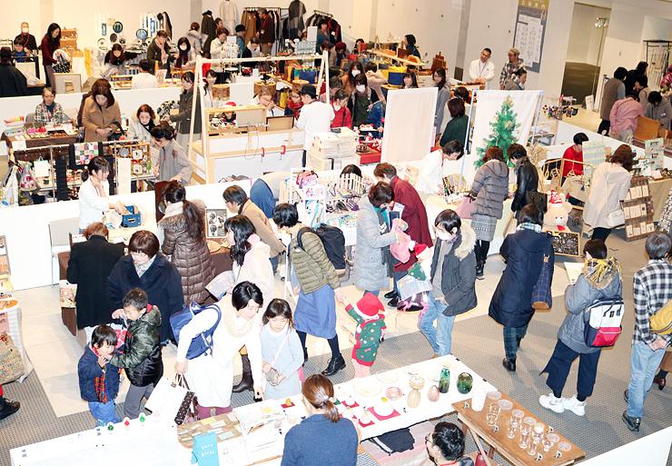 36組の多彩な作品が並ぶ会場を回る来場者=富山市民プラザ