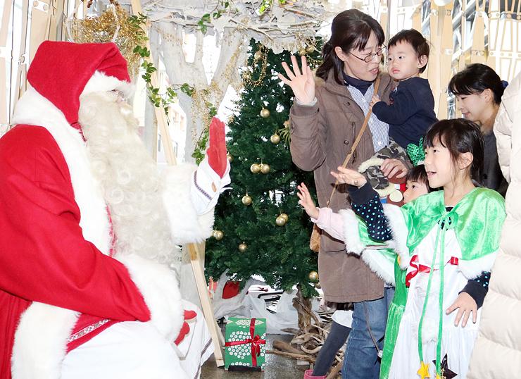 サンタクロースと交流する子どもたち=富山市民プラザ