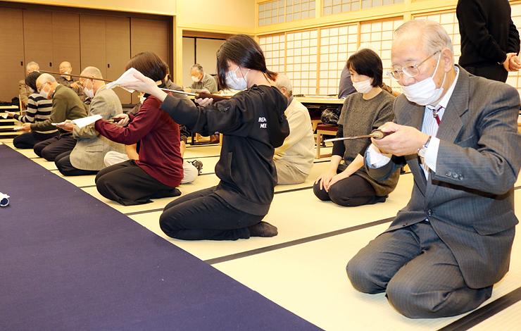日本刀を光にかざし、地鉄や刃文から作者を推理する参加者=森記念秋水美術館