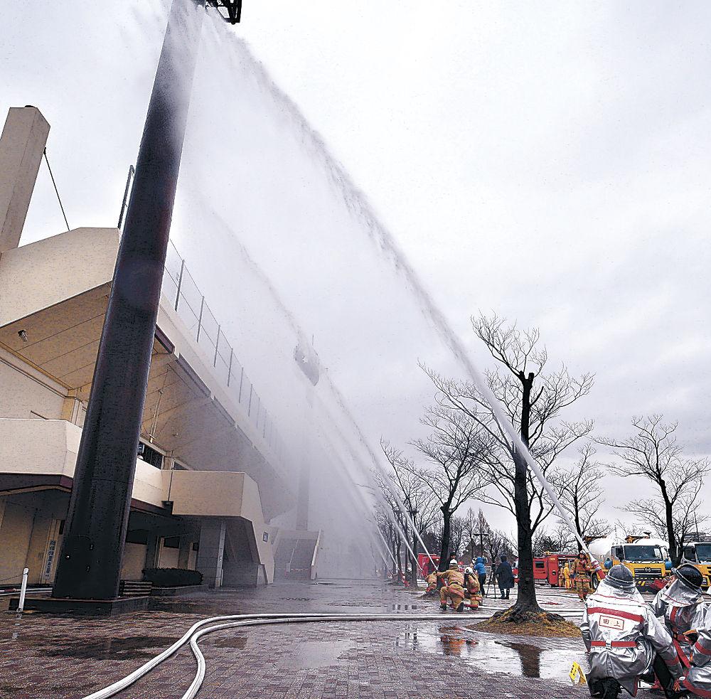 放水銃を使い「水のカーテン」をつくる消防隊員=金沢市城北市民運動公園
