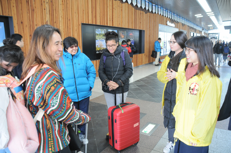 外国人観光客の相談に乗る黄色いジャンパーを着たボランティア団体のメンバー