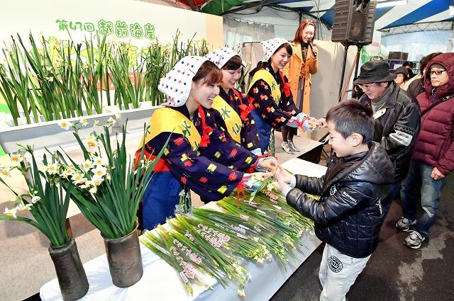 水仙まつりが開幕し、来場者に笑顔で水仙を配る水仙娘=16日、福井県越前町厨の道の駅「越前」