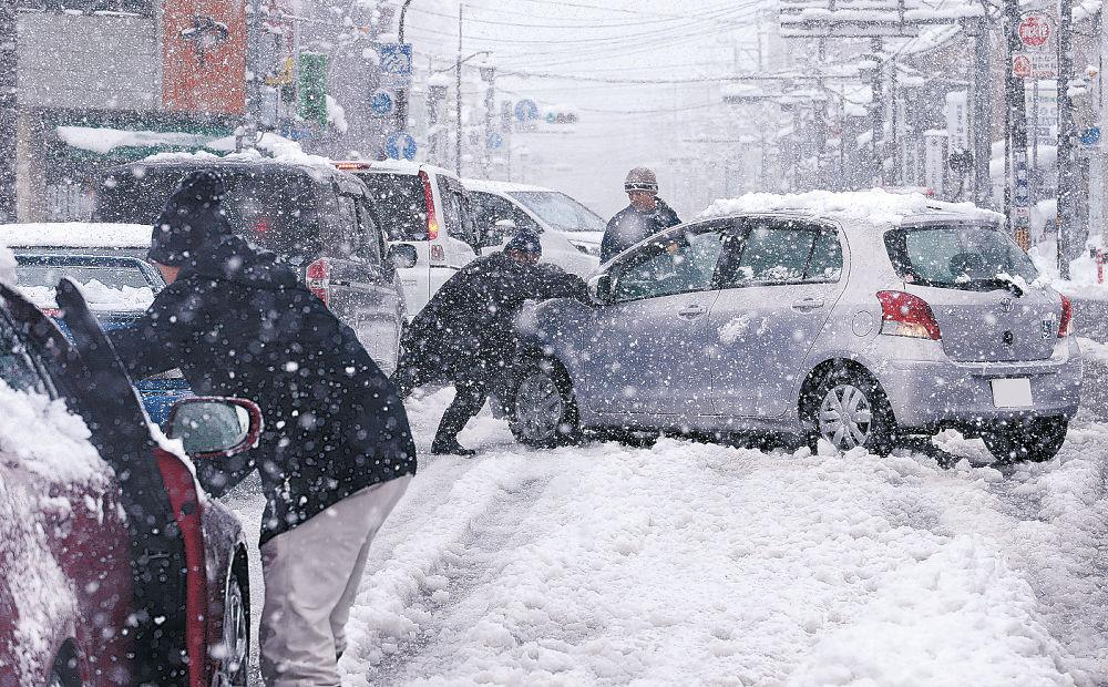 雪にはまり動けなくなった車=17日午前11時半、金沢市寺町1丁目