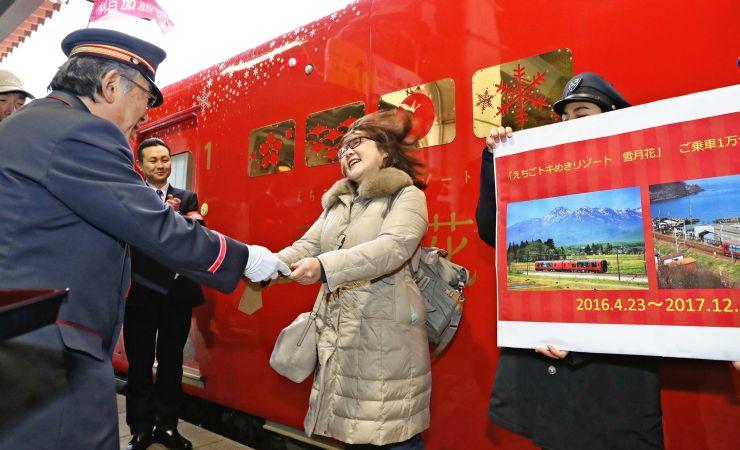 「雪月花」の1万人目の乗客となり、記念品を受け取る女性=17日、糸魚川市の糸魚川駅