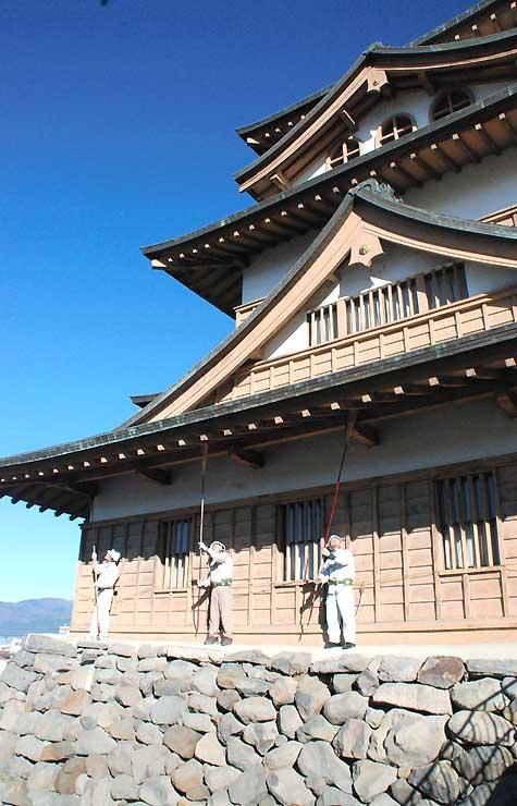 高島城天守閣のひさしにたまったほこりなどをほうきで払う諏訪市職員
