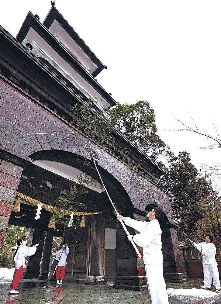 神門の汚れを落とす神職と巫女=金沢市の尾山神社