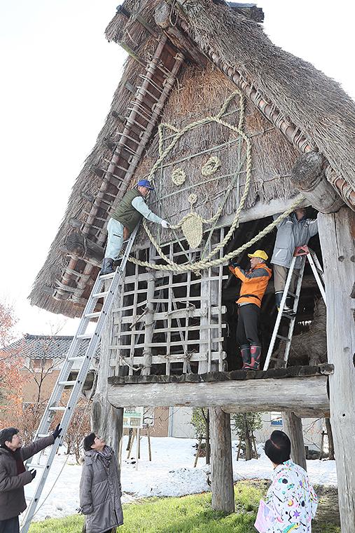 高床建物に犬の顔をかたどった縄文しめ縄を飾る会員=桜町JOMONパーク