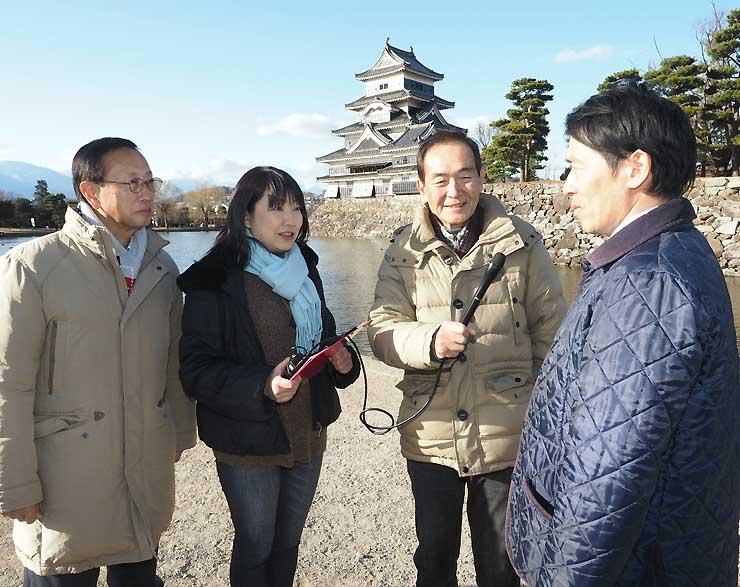 松本城公園で松本市職員(右)にインタビューする中島さん(左から2人目)ら番組出演者ら