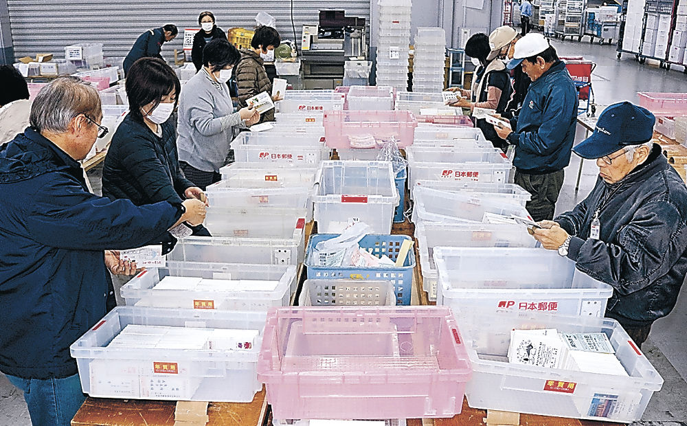 年賀状を仕分けする従業員=金沢市の新金沢郵便局