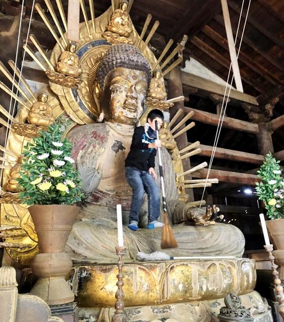 木造釈迦如来坐像に登り、ほうきでほこりを払う少年団員=23日、福井県小浜市国分の国分寺