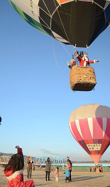 気球に乗ったサンタクロースに手を振る子ども=佐久市