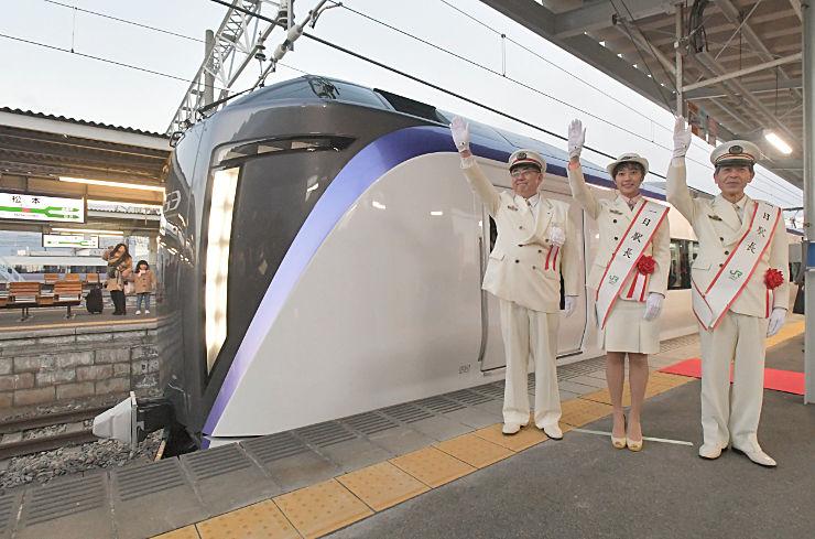 北島駅長(左)らの合図で松本駅を出発する特急スーパーあずさの新型車両「E353系」=23日午前6時51分、松本市