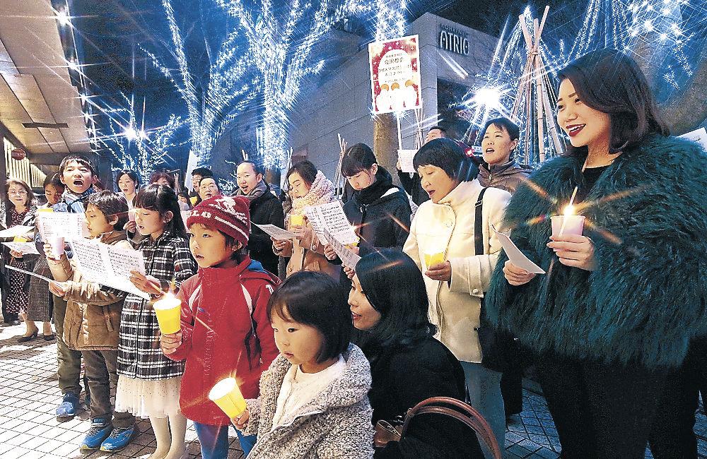 賛美歌を披露する参加者=24日午後5時50分、金沢市の香林坊東急スクエア前(クロスフィルター使用)