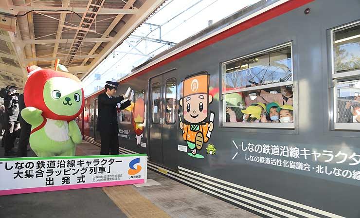 軽井沢駅を出発するラッピング列車。沿線地域のキャラクターが車両に施されている