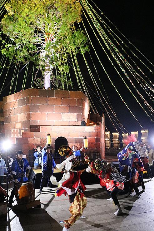 点灯されたクリスマスツリーの前で勇壮な舞を見せる氷見獅子方連中=神戸メリケンパーク