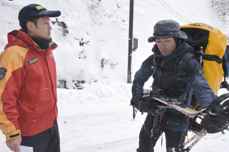 登山者(右)に行程を尋ね、注意を促す県警山岳遭難救助隊員=松本市安曇