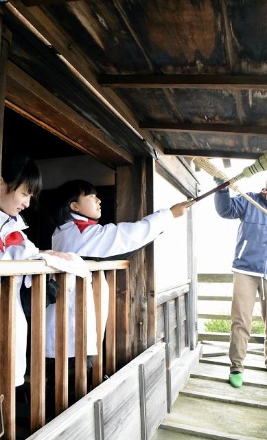 天守の軒下などを掃除する参加者=28日、福井県坂井市の丸岡城