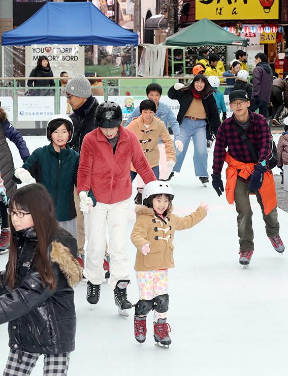 樹脂のスケートリンクで滑りを楽しむ家族連れや若者たち=グランドプラザ