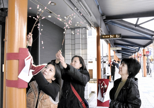 アーケードの柱にもち花を飾り付ける会員=30日、敦賀市神楽町1丁目