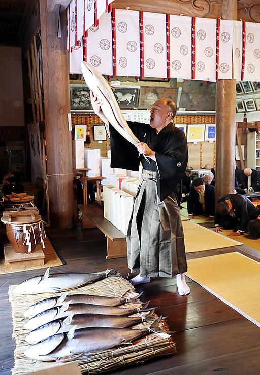 ブリを持ち上げて神前にささげる氏子代表=下村加茂神社