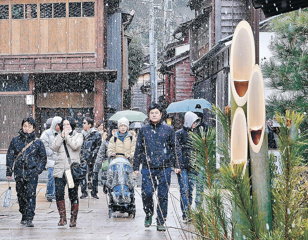 雪の舞う中、散策を楽しむ観光客=金沢市のひがし茶屋街
