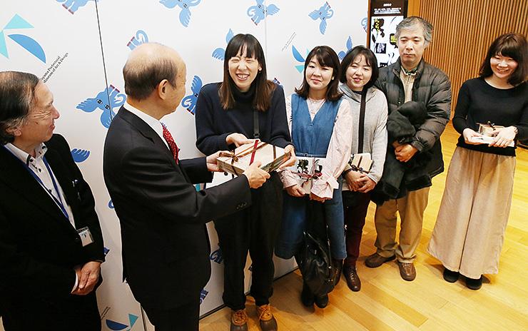 100万人目の来館者となった広瀬さん(左から3人目)に記念品を贈呈する石井知事=富山県美術館