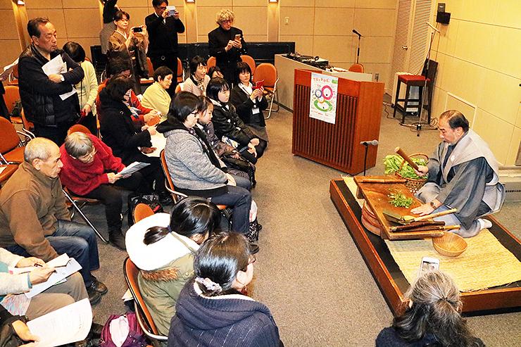 大友さん(右)が行う「七草の行事」に見入る受講者=高岡市万葉歴史館