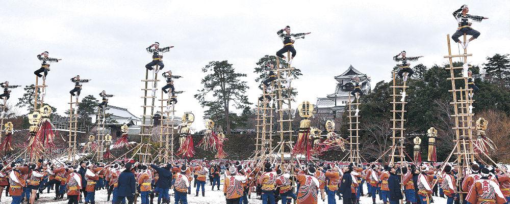 加賀鳶梯子登りで一糸乱れぬ技を披露する消防団員=金沢城公園新丸広場
