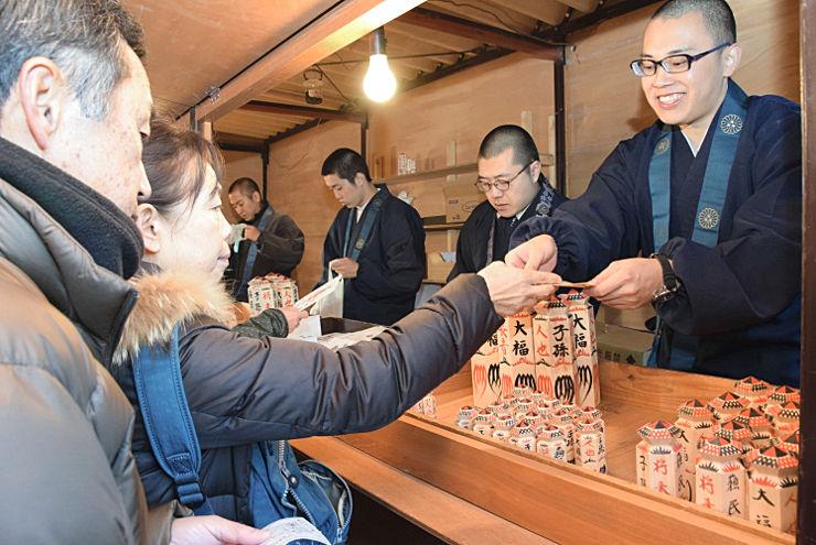八日堂縁日で蘇民将来符を買い求める参拝客ら(左)