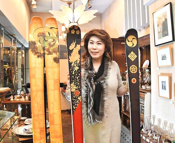 「REINEDEER」のスキー板を手にする高木さん。金箔や漆、螺鈿といった伝統工芸で仕上げている=東京