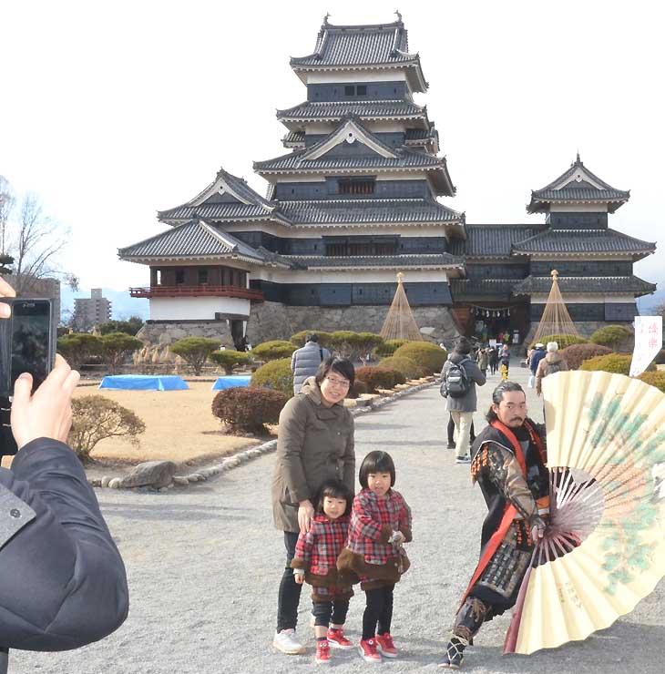 松本城を背に記念撮影する家族連れ。年末年始の来訪者は、前年を下回った=1日