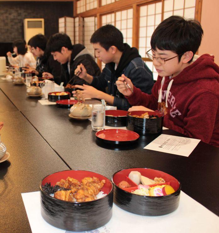 高校受験突破を願い「謙信勝負飯」を食べる生徒ら=8日、上越市吉川区