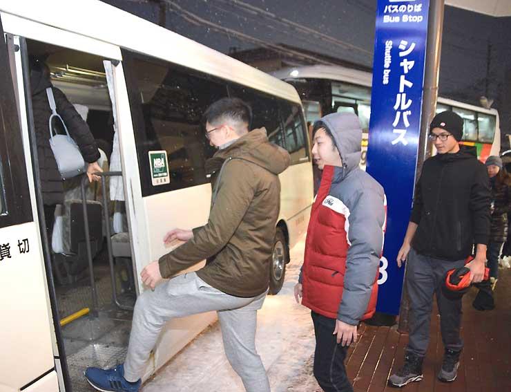 「糸魚川シーフードシャトルバス」に乗り込む香港からのスキー客たち=白馬村
