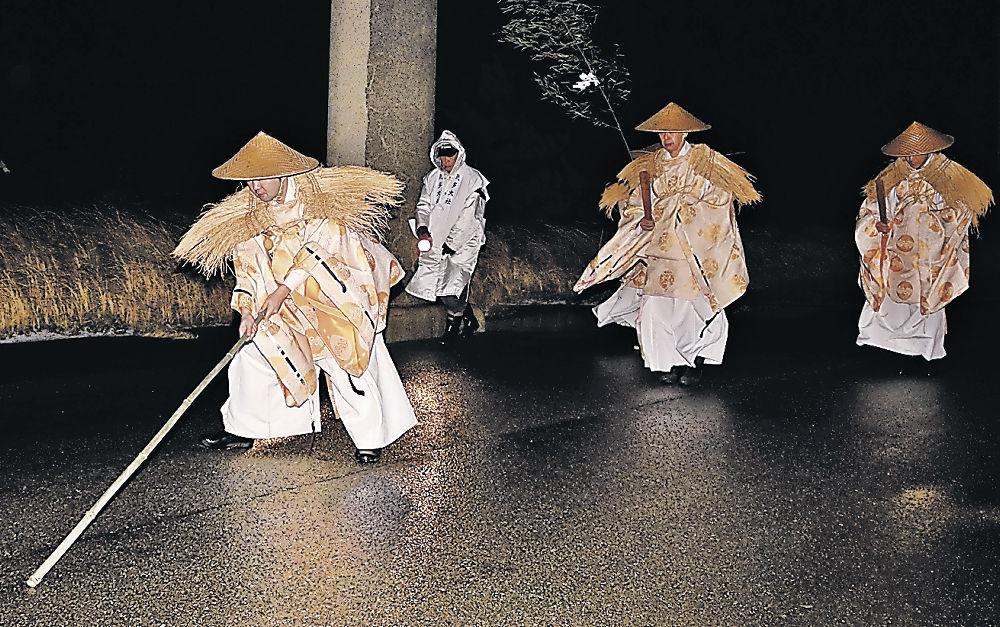 無言で巡拝し、地面に鳥居を描く神職=羽咋市寺家町