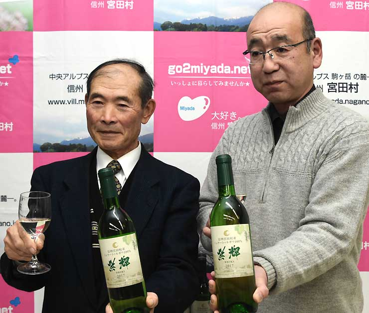 白ワインの「紫輝」のボトルを手にする小田切さん(左)と村田さん