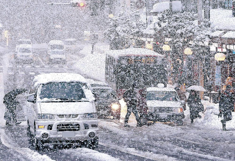雪が降り続いた金沢市中心部を、徐行する車両と足元を気にしながら歩く人=13日午後4時15分、同市香林坊交差点