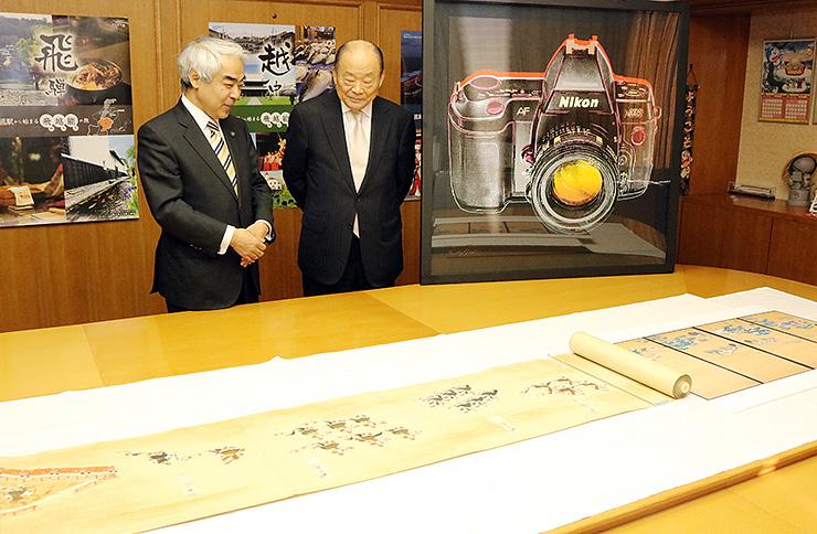 寄贈した美術品を高橋高岡市長(左)に紹介する伊勢さん
