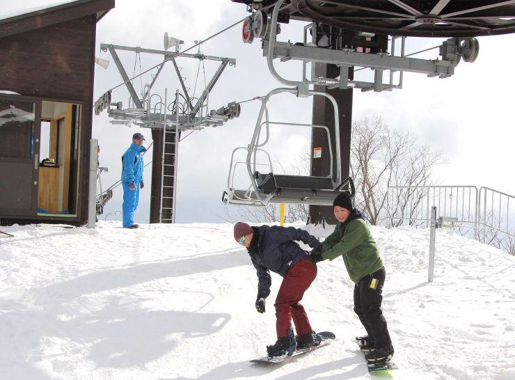 市営平スキー場に新設されたペアリフトから降りるスノーボーダー=13日、佐渡市金井新保
