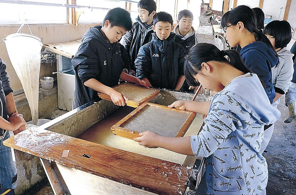 自分たちで集めたガンピの樹皮で紙をすく児童=川北町中島