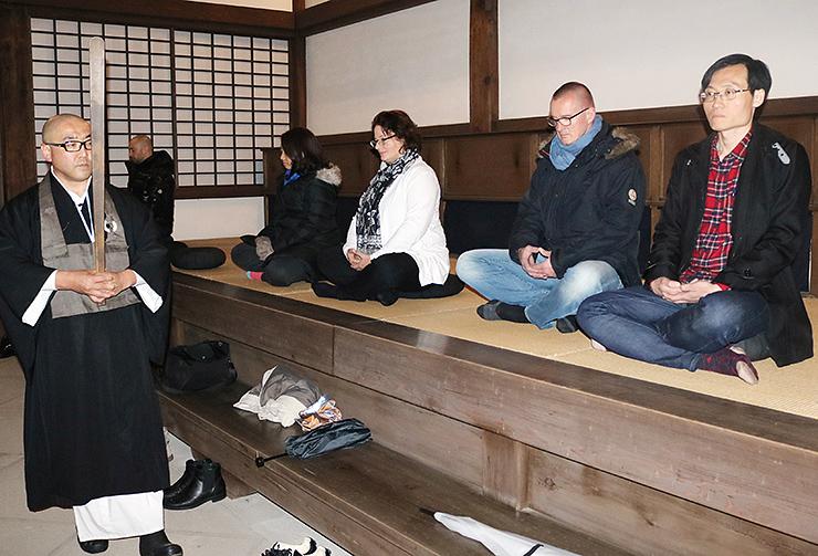 四津谷住職(左)に教わり座禅を体験する参加者