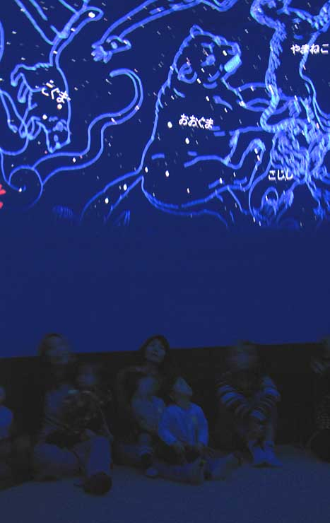 モバイルプラネタリウムで、ドーム内に投影された冬の星空を眺める親子連れたち